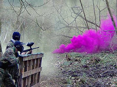 Two people hiding behind a fence and playing paintball outdoors with pink smoke in the foreground
