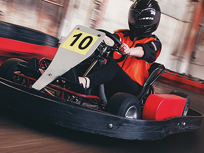 A man racing in a go kart on an indoor track