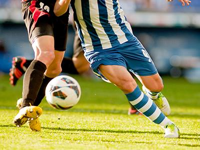 The legs of two men, in different football kits, playing football