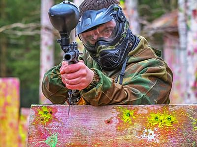 A man in a paintball mask standing behind a wooden board and aiming a paintball gun