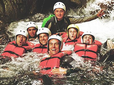 A group of people wearing helmets and life-vests floating in river rapids
