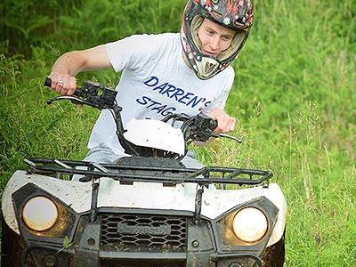A boy wearing a stag do t-shirt, driving a quad bike