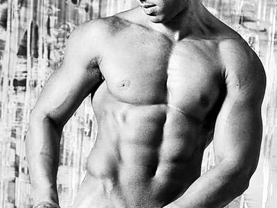 A black and white image of a topless, muscly man