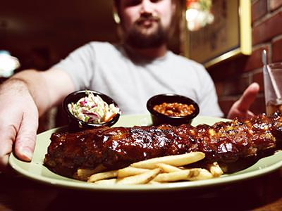A plate of ribs and chips, with a man in the background