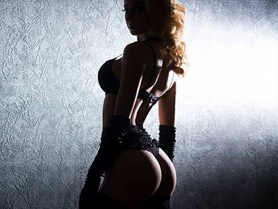 A dimly lit woman poses in black lingerie