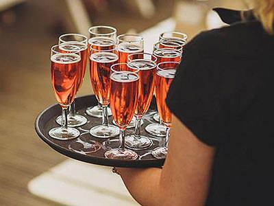 A waitress holding a tray of pink champagne