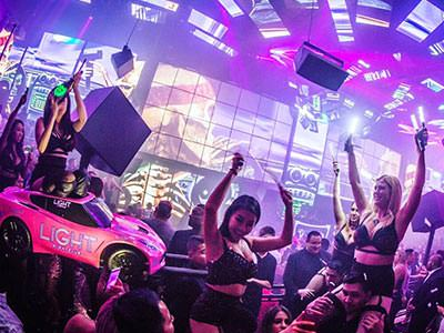 A group of people dancing in a modern nightclub under pink lights