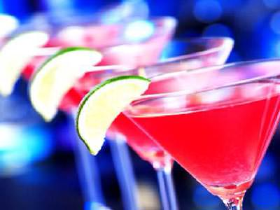 Three red cocktails lined up with slices of lime on the side