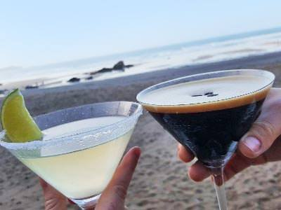 Two people toasting with two cocktails