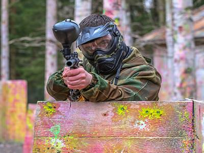 Close up of a man standing behind a fence and holding a paintball gun above the top of it