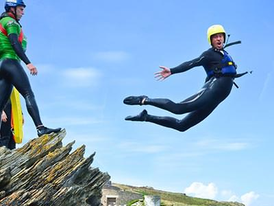 A man jumping off a cliff in a wetsuit, whilst someone looks on