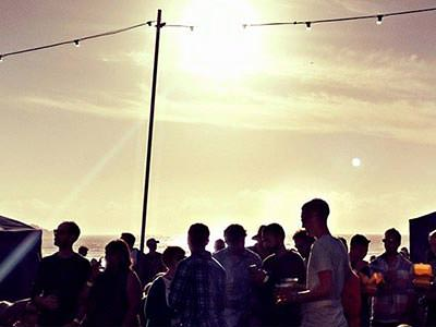 People partying outdoors, under a blazing sun
