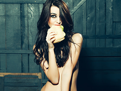 A naked woman eating a burger