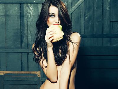 A naked woman eating a burger