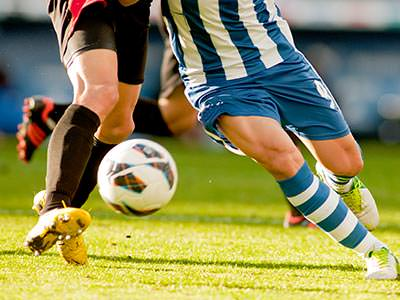 Two players challenge for a football