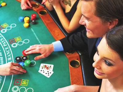 A top-down shot of a group of people playing blackjack