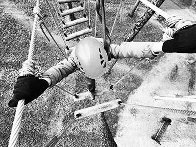 Black and white image of a woman crossing a rope ladder outdoors
