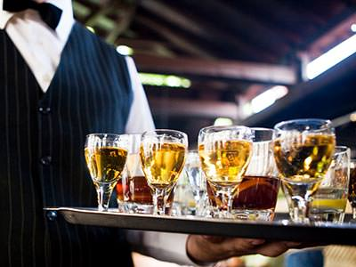 A waiter holding a tray of various drinks