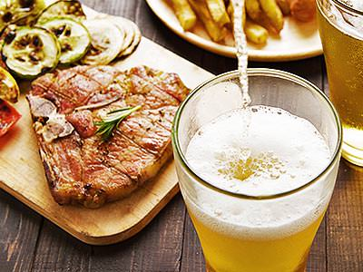 A steak on a wooden board with chips on a plate in the background and a drink being poured