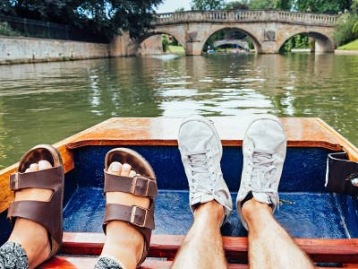 A woman's feet and a man's feet on a boat, with the river and a bridge in the background