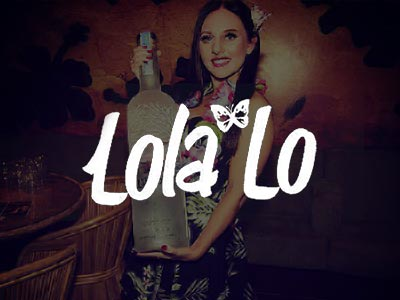A woman in a lei garland, holding a large bottle of vodka in a club
