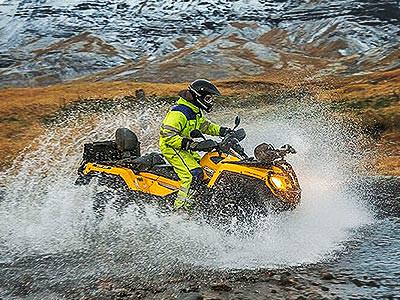A yellow quad bike being driven through a large amount of water