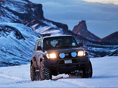 A 4x4 vehicle with large off-road tyres driving over a large expanse of snow