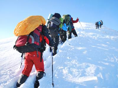 A line of people trekking through thick snow, carrying large packs