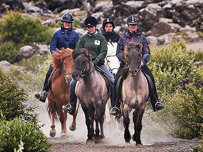 Four horses and and jockeys riding down a dirt path