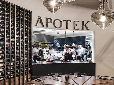 A view of the kitchen through the 'pass-through' at Apotek restaurant, next to a tall wine rack
