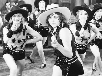 Black and white image of women dressed as cowgirls, pointing and line dancing