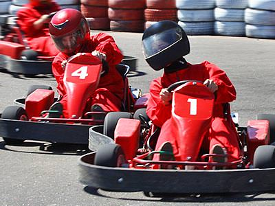 Three men driving go karts around a track