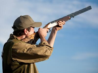 Close up of a man aiming a shotgun to a backdrop of the sky