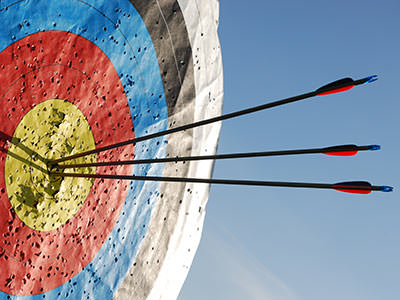 Three bows in a colourful archery target to a backdrop of the sky