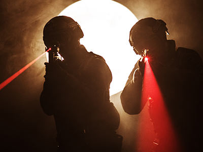 Close up silhouettes of two men aiming red laser beams with laser guns