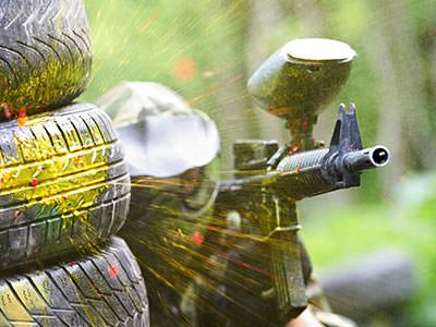 A man hiding behind tyres, aiming his paintball gun