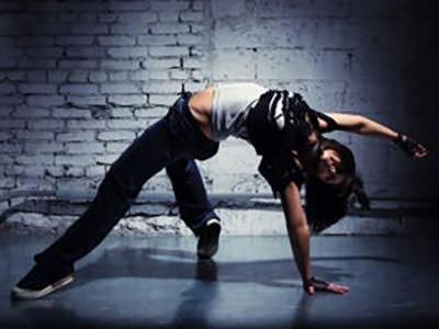 A woman dancing on a grey floor in front of a white wall