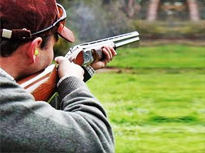 A man wearing a cap, firing a gun into the distance