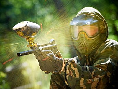 Close up of a man firing a paintball gun whilst wearing a mask and camouflage gear