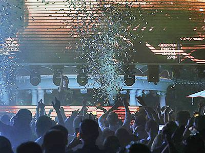A group of people dancing in a modern nightclub under falling confetti