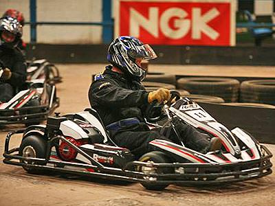 Two people riding go karts around an indoor track