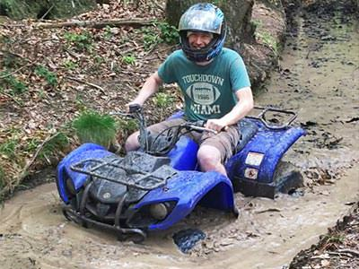 A man stuck in mud on a blue quad bike
