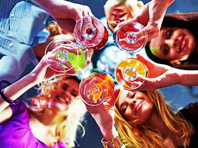 A shot looking up at a group of women holding their drinks in front of them in a circle