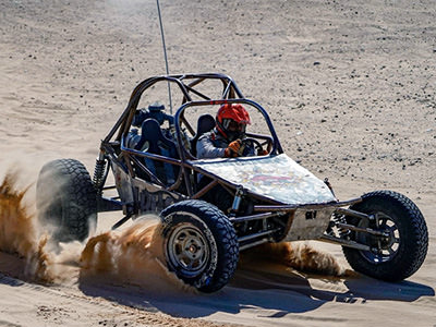 A man posing in the passenger seat of a 4-seater off-road buggy