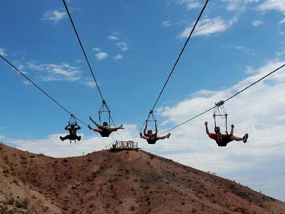 Four people descending a long zipline from a mountain in the desert