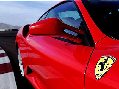 A close up of a red Ferrari car on a racetrack