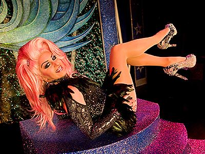 A drag queen reclining back on glitter stairs