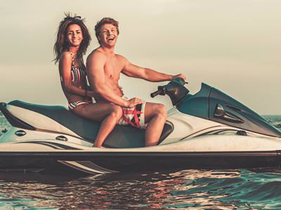 A man and woman sat on a jet ski in the sea