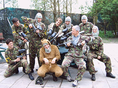 A group of men aiming paintball guns at a main dressed in a costume
