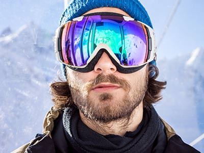 Close up of a man wearing ski goggles and a hat, to a snowy backdrop